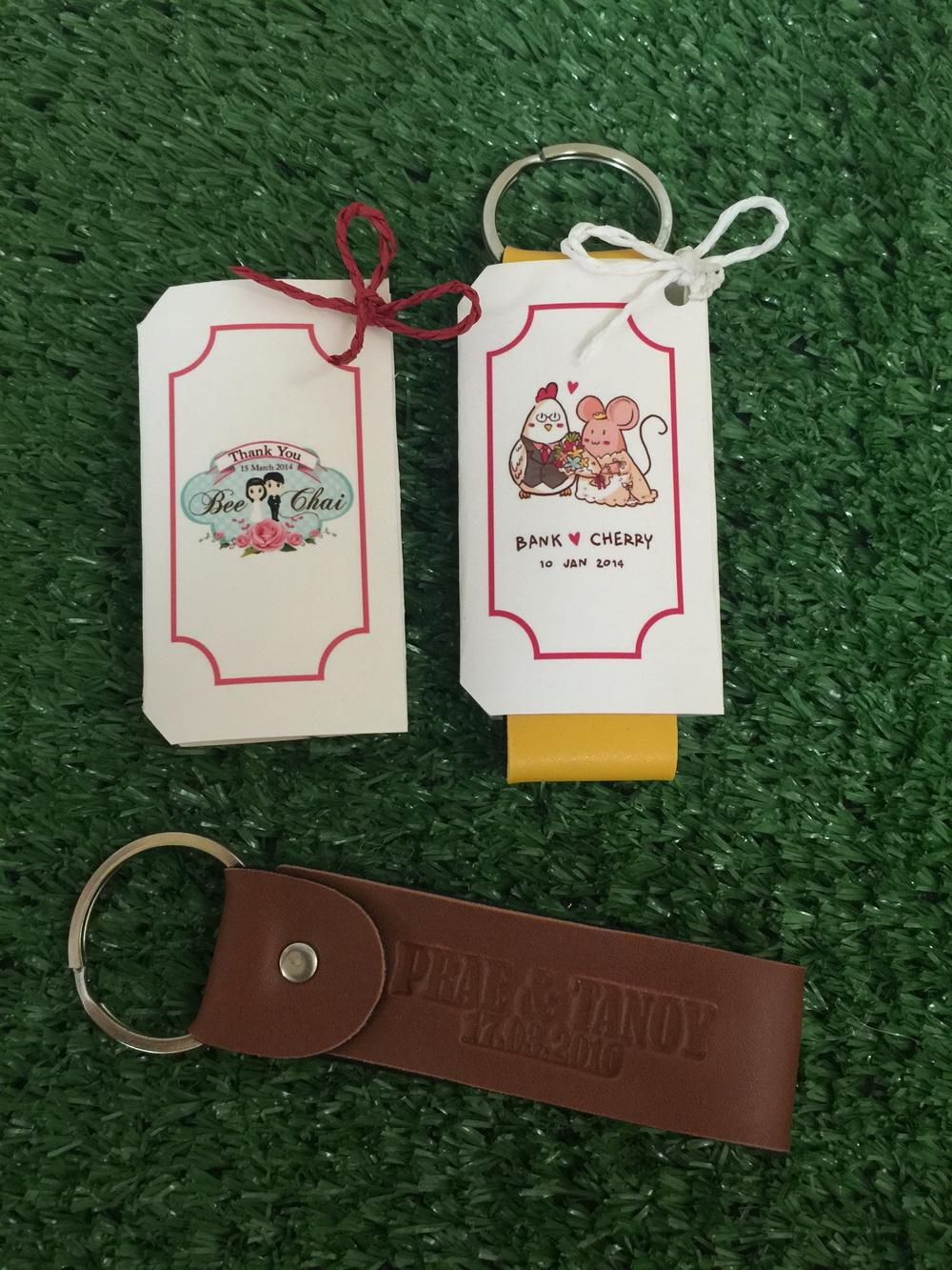 พวงกุญแจหนัง (เลือกสีได้) ปั๊มชื่อและวันที่ แพ็คปลอกกระดาษลายตามแบบ พร้อมพิมพ์ชื่อ